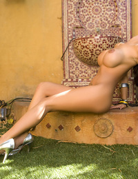 Angelina Valentine moons our cameras with her naked ass and her pierced clit while lounging in the shade near her backyard fountain!