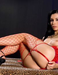 Tristan Kingsley fingers and caresses the red fishnet stockings on her long legs and the garters running across her firm butt and the sheer panties ov